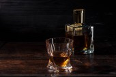 cognac in glass and bottle of luxury alcohol on dark wooden table