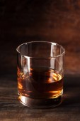 close-up view of glass of luxury amber alcohol on wooden table