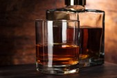 close-up view of glass of whiskey and bottle on wooden table
