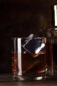 Fotografie Detailní pohled sklenici bourbonu s kostkami ledu a láhev na dřevěný stůl