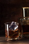 close-up view of glass of cognac with ice cubes and bottle on wooden table