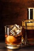 Fotografie Detailní pohled sklenice s kostkami ledu a láhev whisky na dřevěný stůl
