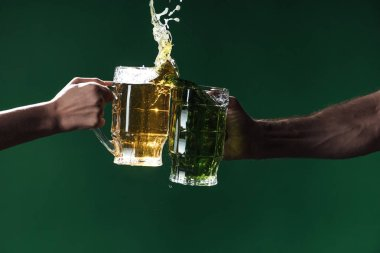 cropped view of men clinking glasses of beer with splashes isolated on dark green, st patrick day concept
