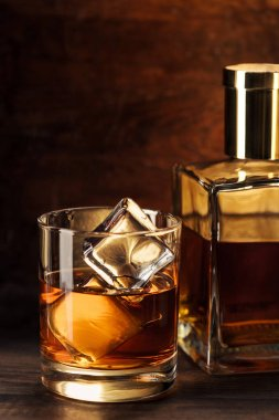close-up view of glass of whisky with ice cubes and bottle on wooden table