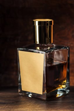 close-up view of luxury cognac bottle with blank label on wooden table