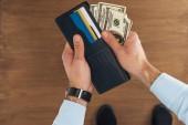 Fotografie pohled shora uvedení dolarů bankovky v peněžence s kreditními kartami na dřevěné pozadí člověka