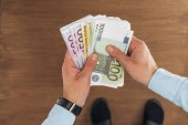 Fotografie top view of man holding euros banknotes on wooden background