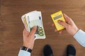 pohled shora člověka drží euro bankovky a kalkulačka na dřevěné pozadí