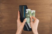 top view of woman puting euros banknotes in wallet on wooden background