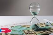 přesýpací hodiny a mince staks na dolar a euro bankovky s šedým pozadím