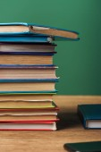 Photo selective focus of stack with books on wooden table and green background