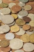 Selektivní fokus různých stříbrných a zlatých mincí na dřevěné pozadí