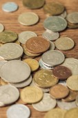 selective focus of silver and golden coins laid out on wooden background