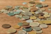 Selektivní fokus stanovené různých mincí na dřevěné rozostřeného pozadí
