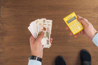 top view of man holding hryvnias banknotes and calculator on wooden background