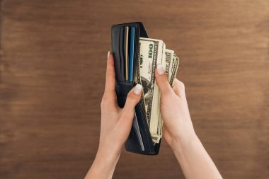 top view of woman puting dollars banknotes in wallet on wooden background