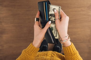 top view of woman taking from wallet dollars banknotes on wooden background