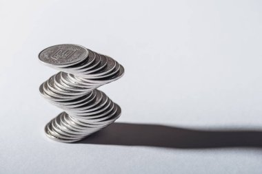 stack of ukrainian silver coins and shadow on grey background