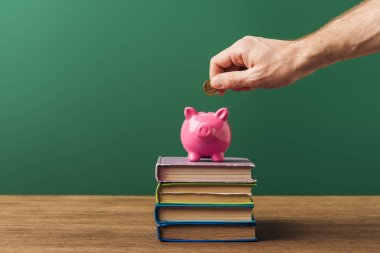 man puting in piggy bank coin on books and wooden table with green background