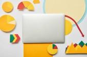 pohled shora laptop a papír diagramů a grafů, ukazatele, list papíru na bílém pozadí