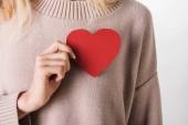 Oříznutý pohled blondýnka v béžové svetru drží papír srdce na bílém podkladu