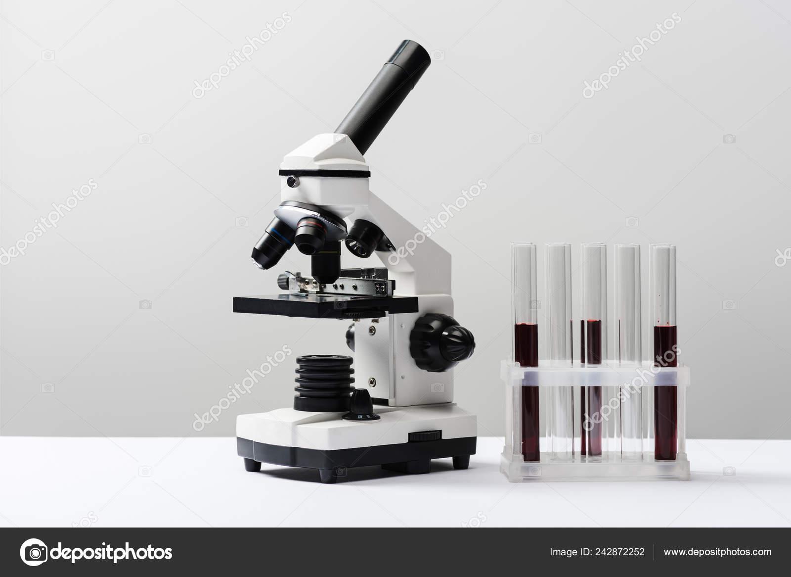 Mikroskop und reagenzgläser mit blut auf grauen hintergrund