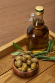 Photo wooden tray with oil bottle, bowl of olives and olive tree leaves on brown surface