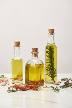 various bottles of oil flavored with rosemary and different spices on white surface