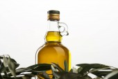 Photo olive tree leaves and bottle of oil isolated on grey