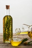 Photo pouring olive oil from bottle into glass bowl, bottle of oil flavored with rosemary, olive tree leaves and olives on wooden surface