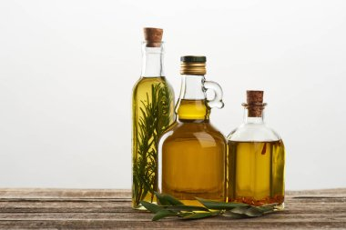 Bottles of olive oil flavored with rosemary and spices isolated on grey stock vector