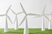 Fotografia modelli di mulino a vento su erba e fondo bianco