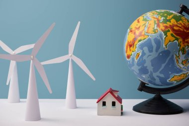 windmill and house models with big globe on white table and blue background