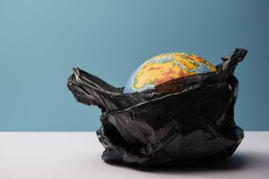 globe in black polyethylene bag on white table and blue background