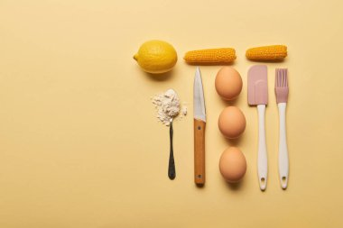 flat lay with kitchenware and ingredients on yellow background with copy space