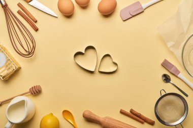 top view of bakery ingredients and cooking utensils around heart shaped dough molds