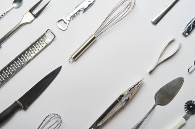 flat lay with metal cooking utensils on grey background