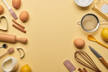top view of bakery ingredients and kitchenware on yellow background