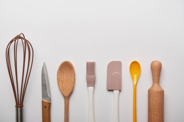 top view of cooking utensils arranged in row on grey background