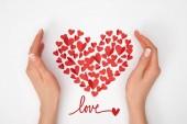 Fotografia vista potata di mani femminili vicino a disposizione della piccola carta rossa a forma di cuore taglia i cuori con scritta love