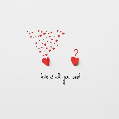 top view of two red paper cut hearts on white background with