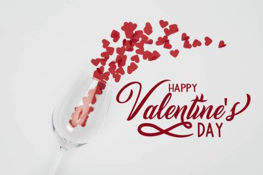 Top view of wine glass and small paper cut hearts on white background with