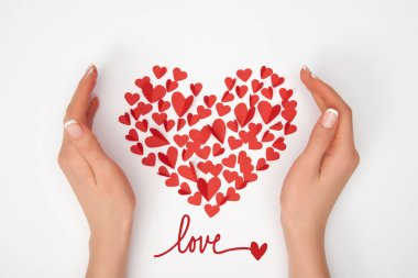 cropped view of female hands near heart shaped arrangement of small red paper cut hearts with