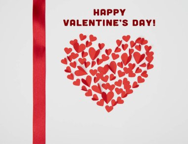 Heart shaped arrangement of small red paper cut hearts with satin ribbon on white background with