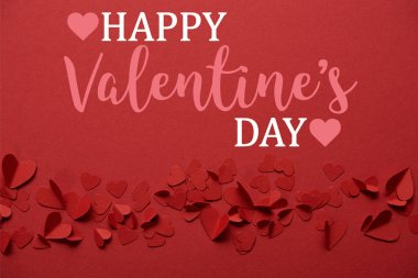 Pile of decorative paper cut hearts on red background with