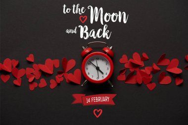 top view of clock and red paper cut decorative hearts on black background with