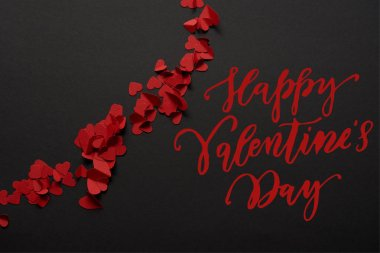 Top view of red small paper cut hearts on black background with