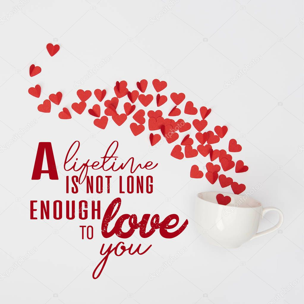 Top view of cup and heap of red paper cut hearts on white background with