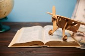 Photo Selective focus of book and toy plane on wooden table