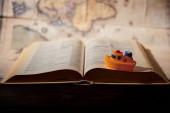 Fotografie Selektivní fokus hračka lodi, knihy a mapy na stole